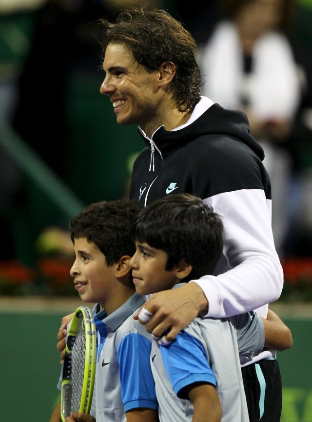 Rafael Nadal of Spain poses with boys after his Qatar Open men's singles tennis match against Andrey Kuznetsov of Russia in Doha, Qatar January 7, 2016. REUTERS/Ibraheem Al Omari