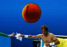 Spain's Rafael Nadal hands plastic to a ball boy as he changes shirt during his first round match against Spain's Fernando Verdasco at the Australian Open tennis tournament at Melbourne Park, Australia, January 19, 2016. REUTERS/Thomas Peter