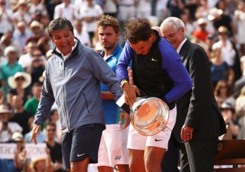 Rafael Nadal of Spain grabs the trophy after victory as coach Toni Nadal looks on during the men's singles final against Stan Wawrinka of Switzerland on day fifteen of the French Open at Roland Garros on June 11, 2017 in Paris, France. (June 10, 2017 - Source: Julian Finney/Getty Images Europe)