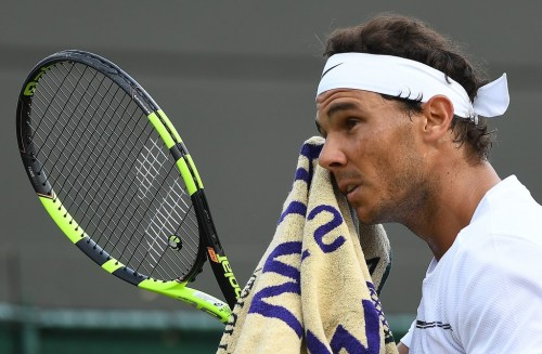 Spain's Rafael Nadal uses a towel during a break in play against Luxembourg's Gilles Muller during their men's singles fourth round match on the seventh day of the 2017 Wimbledon Championships at The All England Lawn Tennis Club in Wimbledon, southwest London, on July 10, 2017. / AFP PHOTO / Glyn KIRK / RESTRICTED TO EDITORIAL USE (July 9, 2017 - Source: AFP)