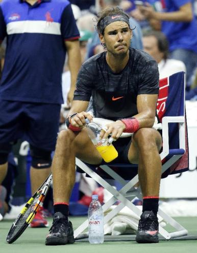 Rafael Nadal, of Spain, rests during the change over after losing a game to Fabio Fognini, of Italy, in the fifth set of a match at the U.S. Open tennis tournament in New York, Saturday, Sept. 5, 2015. (AP Photo/Julio Cortez)