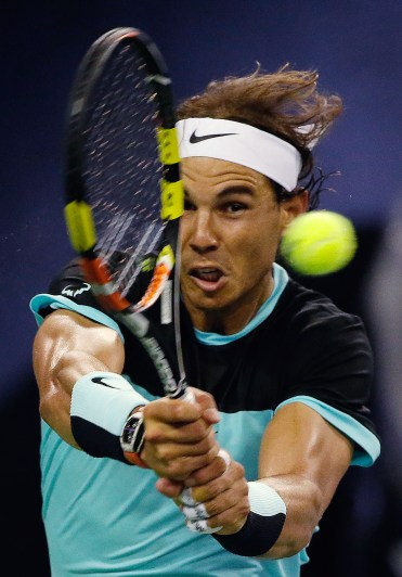 Rafael Nadal of Spain hits a return shot as he plays against Milos Raonic of Canada during their Shanghai Masters tennis tournament in Shanghai, China, Thursday, Oct. 15, 2015. (AP Photo/Andy Wong)