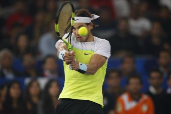 Rafael Nadal of Indian Aces returns a shot to Roger Federer of UAE Royals in the men's singles event of the International Premier Tennis League in New Delhi, India, Saturday, Dec. 12, 2015. (AP Photo /Tsering Topgyal)