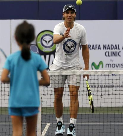 Spanish tennis player Rafael Nadal (R) plays tennis with a young girl during a 'tennis clinic' of his Rafa Nadal Academy with Filipino children in Manila, Philippines, 06 December 2015. Nadal is in Manila with other current and former international male and female tennis aces to compete in the International Premier Tennis League (IPTL). (Tenis, Filipinas) EFE/EPA/FRANCIS R. MALASIG