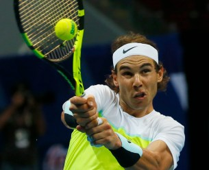 Spain's Rafael Nadal of the Indian Aces returns a shot to Canada's Milos Raonic of the Philippine Mavericks during the men's singles match of the 2015 International Premier Tennis League Tuesday, Dec. 8, 2015 at the Mall of Asia Arena at suburban Pasay city south of Manila, Philippines. Nadal won the thrilling shootout 6-5 (7/6). (AP Photo/Bullit Marquez)