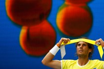Spain's Rafael Nadal sits in his chair as he puts on a new head band during his first round match against Spain's Fernando Verdasco at the Australian Open tennis tournament at Melbourne Park, Australia, January 19, 2016. REUTERS/Thomas Peter