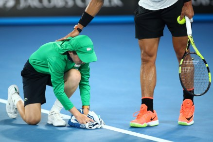 A ball kid wipes sweat on the court from Rafael Nadal of Spain in his fourth round match against Gael Monfils of France on day eight of the 2017 Australian Open at Melbourne Park on January 23, 2017 in Melbourne, Australia. (Jan. 22, 2017 - Source: Cameron Spencer/Getty Images AsiaPac)