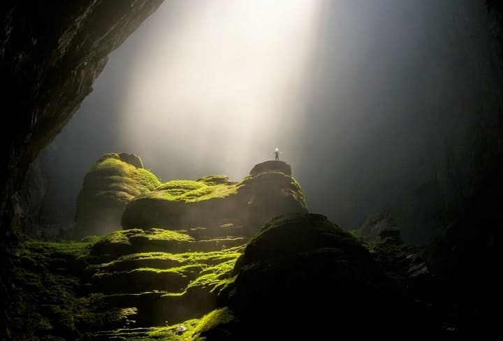 person in a large cave standing in awe