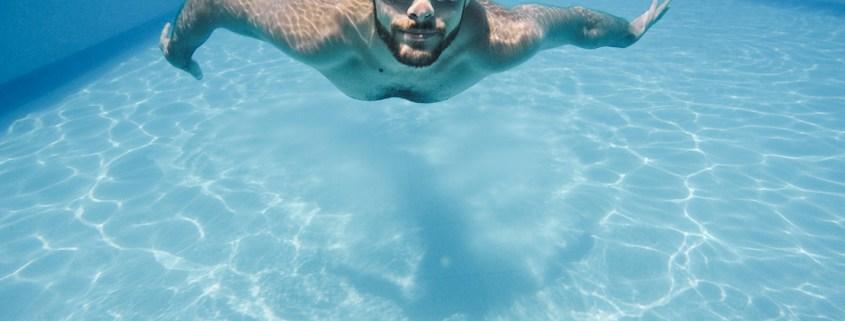 Noi bussejant amb ulleres en una piscina.