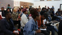 An audience of mostly young people, listen intently to a Creative Hustle panel discussion about Innovative collaborations in the digital space hosted by Livity Africa.