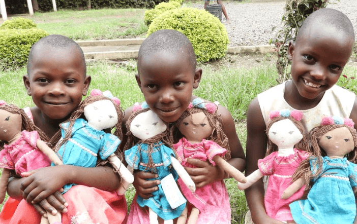 Three girls holding dolls