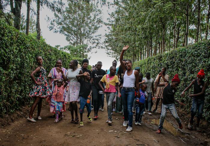 Staff and children walk down driveway at Doyle Farm in Kenya