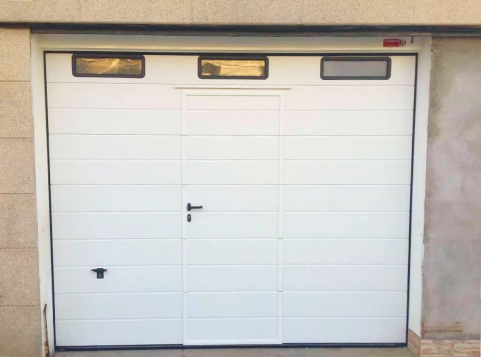 Puerta seccional ISO-45 con peatonal incorporada
