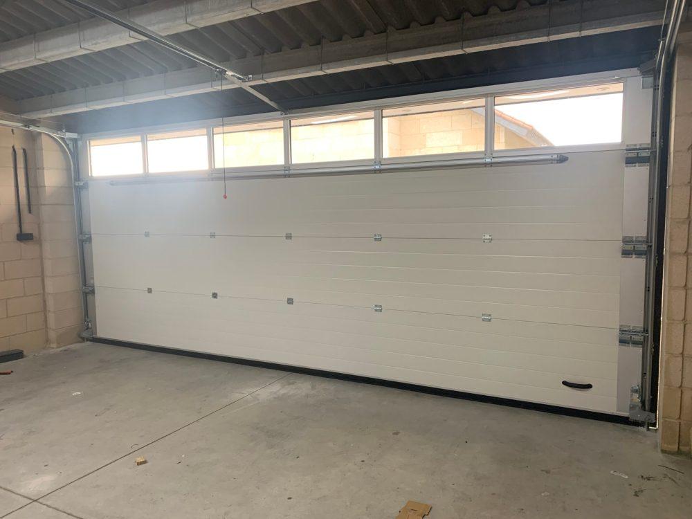Puerta seccional Novoferm Thermo ISD2 con franja acristalada, instalada en Cambados 4