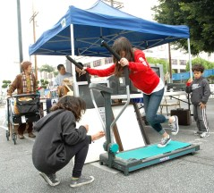 Some youngsters get a workout while trying out a treadmill. (Mikey Hirano Culross/Rafu Shimpo)