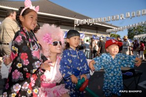 "HappyFunSmile singer Akiko ""Kewpie"" Hiroshima gets some face time with youngsters enjoying the festivities. (MIKEY HIRANO CULROSS/Rafu Shimpo)"