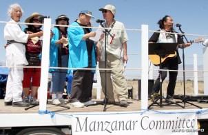 """Ken Koshio (right) leads the gathering in a sing-along performance of Kyu Sakamoto's """"Sukiyaki."""""""