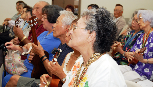 Residents of Keiro practice strumming, under the guidance of Arimoto.