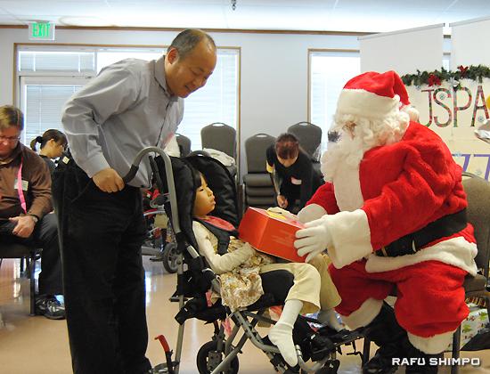 「サンタクロース」からプレゼントを手渡される瀧口真菜ちゃん。後ろは父親の好重さん