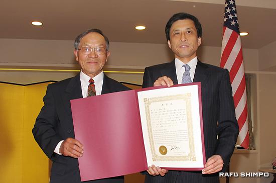 新美潤総領事(右)から表彰状を授与される西さん