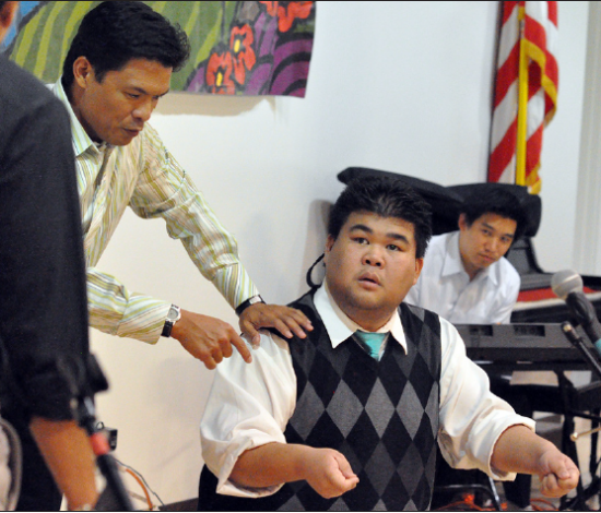 """Cold Tofu cast member Shannon Wong (seated) instructs teammate Michael Palma on the finer points of """"brain surgery"""" during last year's South Bay performance at the Gardena Valley Japanese Cultural Institute. (Photo by Jeff Murakami)"""