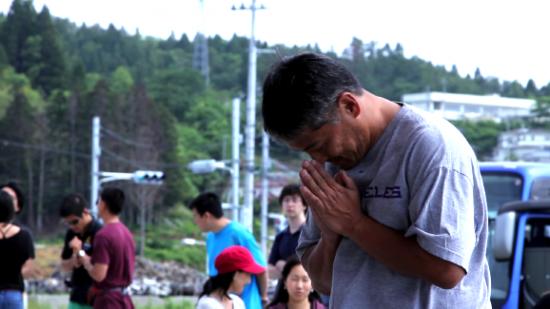 Los Angeles photojournalist Darrell Miho praying at a makeshift shrine.