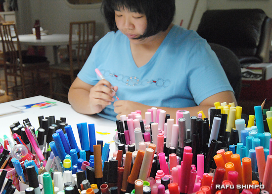Surrounded by many colorful markers, Hikaru enjoys drawing.