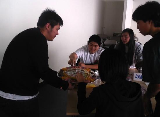 Nathan Tadios serves manju from Fugetsu-Do Confectionery to Rising Stars members (from left) Derek Manaka, Dani Yang, Hiro Ozaki and Sharyse Watanabe.