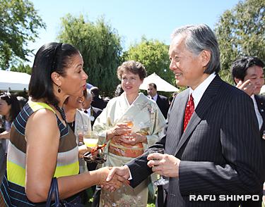 招待客と握手し、自己紹介する堀之内総領事(右)