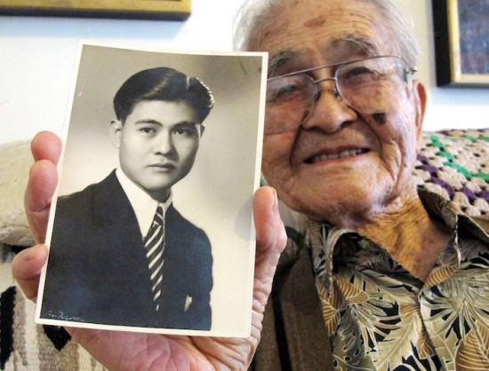 """Masao Yamashiro holds a photo of himself as a young man. Below, a copy of """"Tessaku,"""" a literary journal published in Tule Lake. The journal kept to non-political topics but was still monitored by U.S. governmental authorities. (Photos by MARIO G. REYES/Rafu Shimpo)"""
