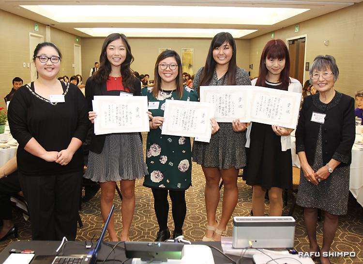 奨学金の授与式。左から奨学金選考委員の目時ジョアンナさん、受賞者の西さん、中川さん、松本さん、飯塚さんと、難波会長