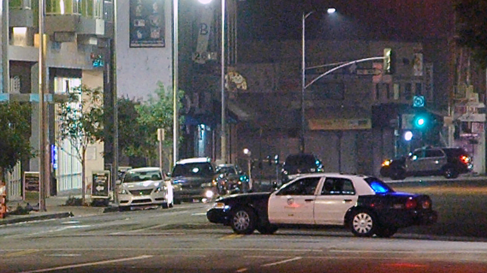 A white Nissan Altima (left) is inspected by an LAPD Bomb Squad robot, Friday in Little Tokyo. (MIKEY HIRANO CULROSS/Rafu Shimpo)