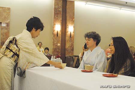 平田さんから新年の茶を提供される堀之内夫人(中央)。右隣は南加日商の柴さん