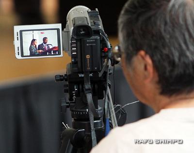 Jan Yen of NCRR videotapes co-emcees Helen Ota and Curtiss Takada Rooks.