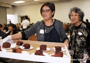 Past awardee Amy Kato helps serve the cake.