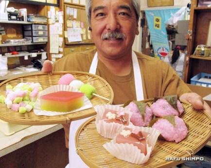 Brian kito: Brian Kito holds a selection of Hinamatsuri manju and yokan, including sakura mochi. (MARIO G. REYES/Rafu Shimpo)