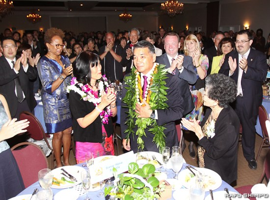 Former LAPD Deputy Chief Terry Hara, with his wife, Gayle, and mother, Yoneko, gets a standing ovation from about 500 well-wishers. Behind him are Consul General Harry Horinouchi and Sheriff Jim McDonnell. (JUN NAGATA/Rafu Shimpo)