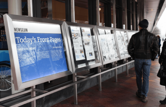 People reading front pages of local newspapers from all over the United States.