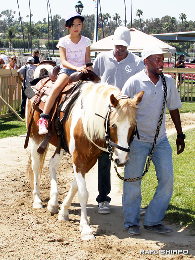 A youngster takes a spin on the course set up for pony rides, with some trusty handlers leading the way.
