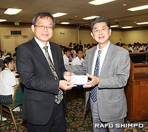 夕食会で、南加愛媛県人会の大谷喜平会長(右)から記念品を贈られる藤田繁治校長