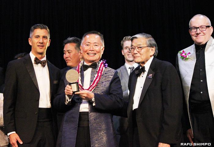 日系社会への貢献をたたえられ(写真左から)キムラ館長から名誉勲章が贈呈されたジョージ・タケイ氏、同氏の受賞を祝福する元連邦運輸長官のノーマン・良雄・ミネタ氏、タケイ氏のパートナーであるブラッド・タケイさん