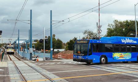 ランチョパーク駅に到着するエクスポライン試験車両(奥)と、踏み切りを通過するサンタモニカ・ビックブルーバス(写真=メトロ提供)