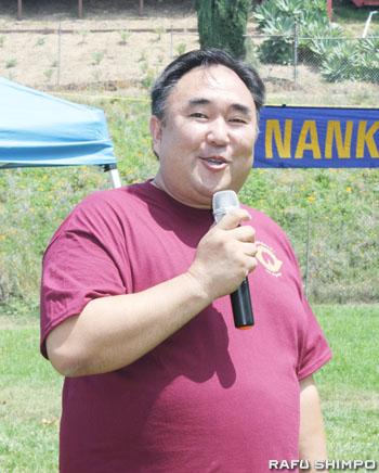 「今年のピクニックも楽しんで下さい」と会員たちに呼び掛けるヨシモト会長