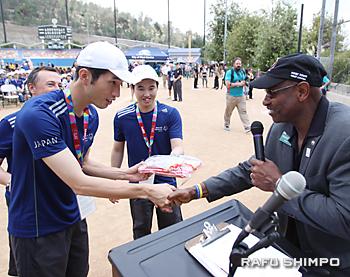 おみやげを手渡し、ウエストコビナ市長(右)と握手する日本アスリートの2人の代表。2人は英語で立派にあいさつした