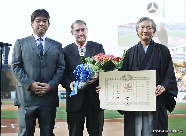旭日中綬章の伝達式で、野茂英雄氏(左)から贈られた花束を抱えるピーター・オマリー氏(中央)。右は堀之内秀久総領事
