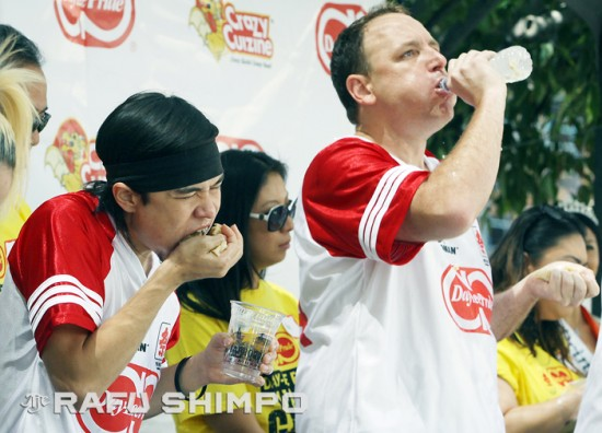 """Matt """"The Megatoad"""" Stonie gobbles gobs of gyoza as rival Joey """"Jaws"""" Chestnut washes his down, during Saturday's Day-Lee Foods World Gyoza Eating Championship at the JACCC Plaza in Little Tokyo. Stonie ate a scant four more dumplings than Chestnut to win the title. (MARIO G. REYES/Rafu Shimpo)"""