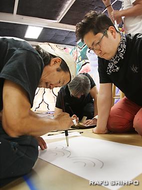 ワークショップの参加者に紙の貼り方を教える柳谷明文さん(左)