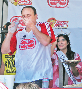 Nisei Week Queen Tori Nishinaka- Leon looks on in disbelief as Joey Chestnut devours handfuls of gyoza at last year's gyoza eating championship in Little Tokyo. Chestnut ate a record 384 of the dumplings in 10 minutes. (J.K. YAMAMOTO/Rafu Shimpo)