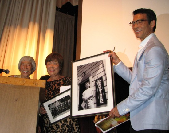 Ruth Matsuo Brandt, daughter of Sei Fujii, presents Nancy Oda of the Tuna Canyon Detention Station Coalition with a photo of Fujii in front of his newspaper, The Kashu Mainichi. At right is emcee David Ono of ABC7.