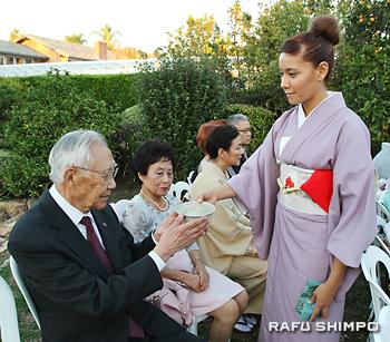 江戸千家小笠原煎茶道の山口弘南加支部長(左)にお茶を出す野本宗智師の弟子
